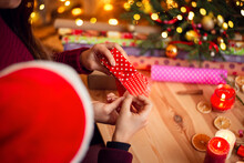 Brother And Sister Preparing Presents For Relatives, Wrapping Them In Paper, Having Good Time Together. Small Boy Helps His Sister With Christmas Presents