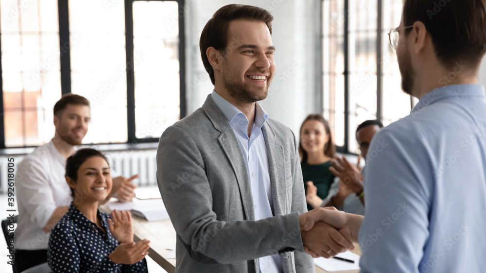 Fototapeta Happy motivated millennial man intern is being hired on regular job employed to international company, loyal young male manager handshaking with leader employer on formal meeting with corporate team