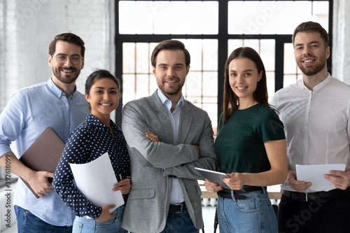 Strategy of success. Confident young male team leader making good career posing for portrait with diverse employees, content customer looking at camera receiving professional support of company staff