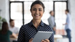 Leinwandbild Motiv Glad to help you. Portrait of smiling confident indian female insurance broker bank manager hr assistant standing in open space office holding digital tablet looking at camera ready to assist client