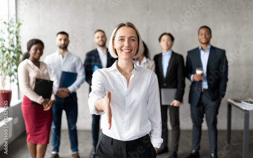 Cheerful Businesswoman Stretching Hand For Handshake Greeting Standing In Office
