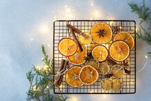 Dried Oranges, Lemons, Cinnamon Sticks And Anise Stars On A Background Of Christmas Lights And Fir Branches. Ingredients For Cooking Or Christmas Decoration. Flat Lay. Space For Text