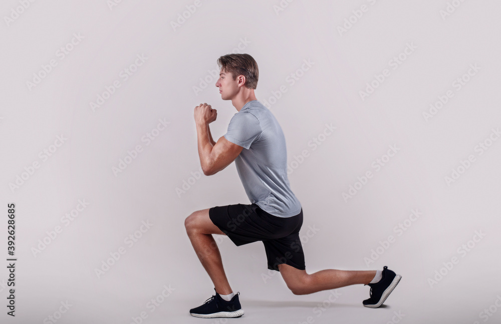 Fototapeta Side view of young fit guy in sportswear doing lunge on light studio background