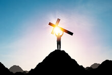 Silhouette Human Holding Cross Or Crucifixion Of Jesus Christian On Top Of Mountain With Sunlight And Clouds Sky. Christianity Religion Concept.