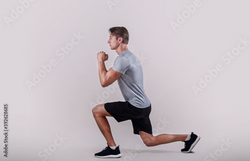 Side view of young fit guy in sportswear doing lunge on light studio background Fototapet