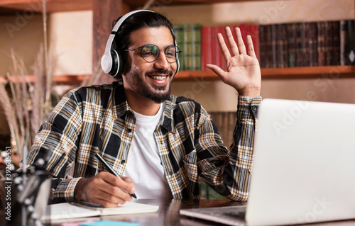 Papel de parede Arab Student Guy At Laptop Waving Hello Learning At Home