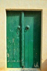 old Traditional wooden green aged Tunisian door with ornament in Kairouan Medina
