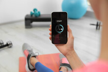 Young Woman Using Fitness App On Smartphone Indoors, Closeup