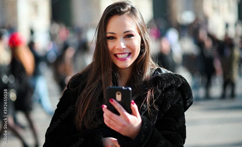 Fototapeta Beautiful young tourist girl in Milan using a smartphone