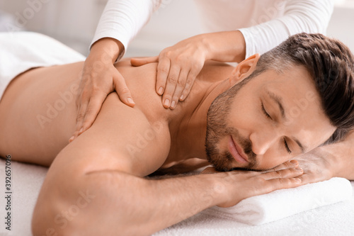 Closeup of handsome man having full body massage at spa