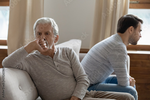 Stampa su Tela Unhappy mature father and adult son not taking after quarrel, sitting on couch a