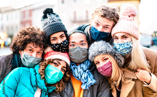 Obraz Multiracial friends taking selfie wearing face mask and winter clothes - New normal lifestyle concept with young people having fun together outside - Bright filter with focus on central asian guy - fototapety do salonu