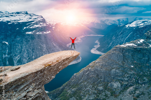 Fototapeta Norway, A woman Jumping on the mountains cliff edge of Trolltunga throning over Ringedalsvatnet  watching the sunset and snowy Norwegian mountains near Odda, Rogaland, Norway obraz