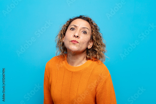 Fotografía middle age woman with a goofy, crazy, surprised expression, puffing cheeks, feel