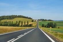 Asphalt Road Cutting Through The Rural Landscape