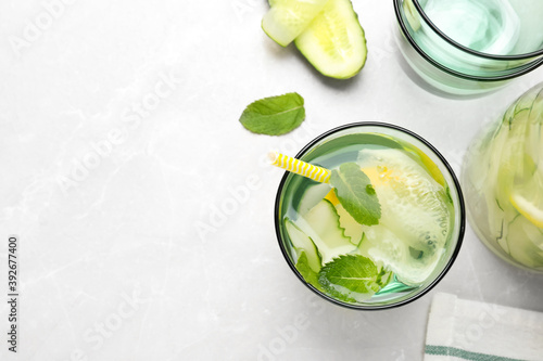 Refreshing water with cucumber, lemon and mint on white table, flat lay. Space for text