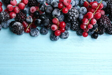 Mix Of Tasty Frozen Berries On Light Blue Wooden Table, Flat Lay. Space For Text