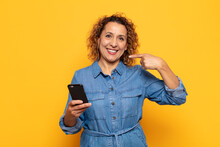 Hispanic Middle Age Woman Smiling Confidently Pointing To Own Broad Smile, Positive, Relaxed, Satisfied Attitude