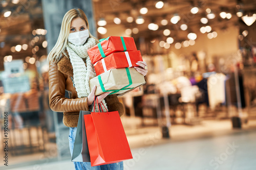 Fotografía Portrait of adult woman shopping in mall wearing a mask, coronavirus concept