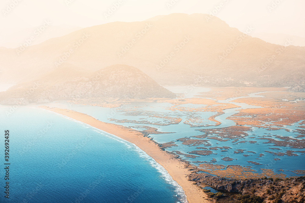 Fototapeta Scenic aerial paniramic view from mountain Bozburun to Iztuzu beach and the Dalyan river Delta as well as lake Sulungur at sunset time. Majestic autumn landscape. Explore natural wonders of Turkey