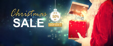 Christmas Sale Message With Santa Opening A Gift Box On A Shiny Light Background