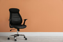 Modern Office Chair Near Orange Coral Wall Indoors. Space For Text