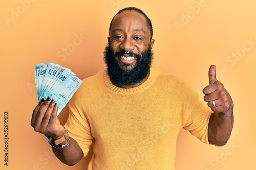 Fototapety, obrazy: Young african american man holding 100 brazilian real banknotes smiling happy and positive, thumb up doing excellent and approval sign