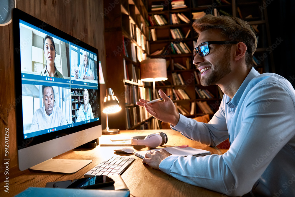 Fototapeta Business man having virtual team meeting on video conference call using computer. Social distance worker working from home office talking to diverse colleagues in remote videoconference online chat.