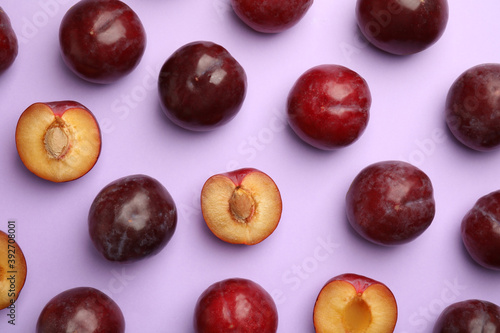 Fotografia Delicious ripe plums on violet background, flat lay