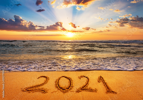 Fototapeta Happy New Year 2021 is coming concept. Number 2021 written on seashore sand at sunrise. obraz