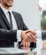 close up. smiling businessman shaking hands with his business partner.