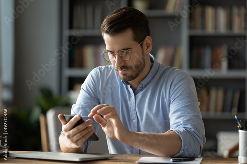 Obraz Serious businessman wearing spectacles using mobile phone sit at desk in cozy office. Manager solve issues with client remotely by modern wireless device, surfing web, learn new business app concept - fototapety do salonu