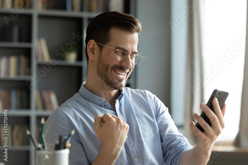 Photo Happy young man sitting at home office room holding smartphone read message feel amazed by great on-line news