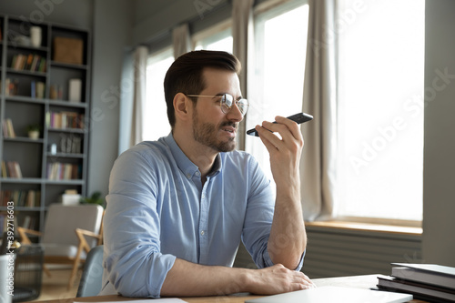 Fényképezés Man sit at desk at home office room holding smart phone communication device using loudspeaker answering to incoming call, leave voice audio message to client remotely