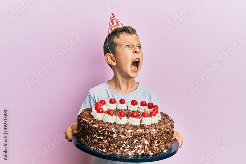 Photographie Adorable caucasian kid celebrating birthday with cake angry and mad screaming frustrated and furious, shouting with anger