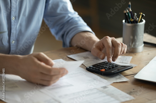 Personal finance management, accounting concept. Close up view man sitting at table using calculator performs arithmetic operations calculates costs per month, manage family budget, control expenses
