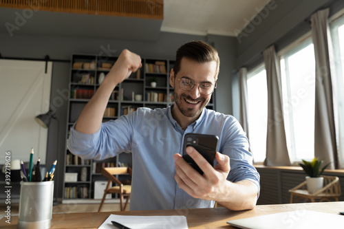 Fotografia Young businessman sitting at desk in home office room looks at smart phone screen reading message, bank notification feels happy celebrate great news by sms