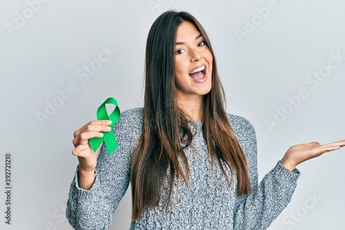 Young brunette woman holding support green ribbon celebrating achievement with happy smile and winner expression with raised hand - fototapety na wymiar