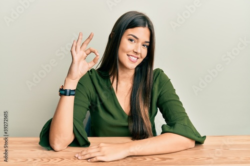 Fototapeta Young brunette woman wearing casual clothes sitting on the table smiling positive doing ok sign with hand and fingers