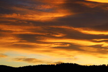 Dramatic Sky In Dawn Over Mountains. Before Sunrise, The Sun Sets Over Scandinavia's Forest And Woods Skyline. The Violent Golden Cloud Is Like A Burning Flame.