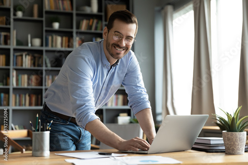 In modern office good-looking businessman young entrepreneur successful business owner standing leaned over workplace desk smile look at camera feels confident. Freelancer or teacher portrait concept