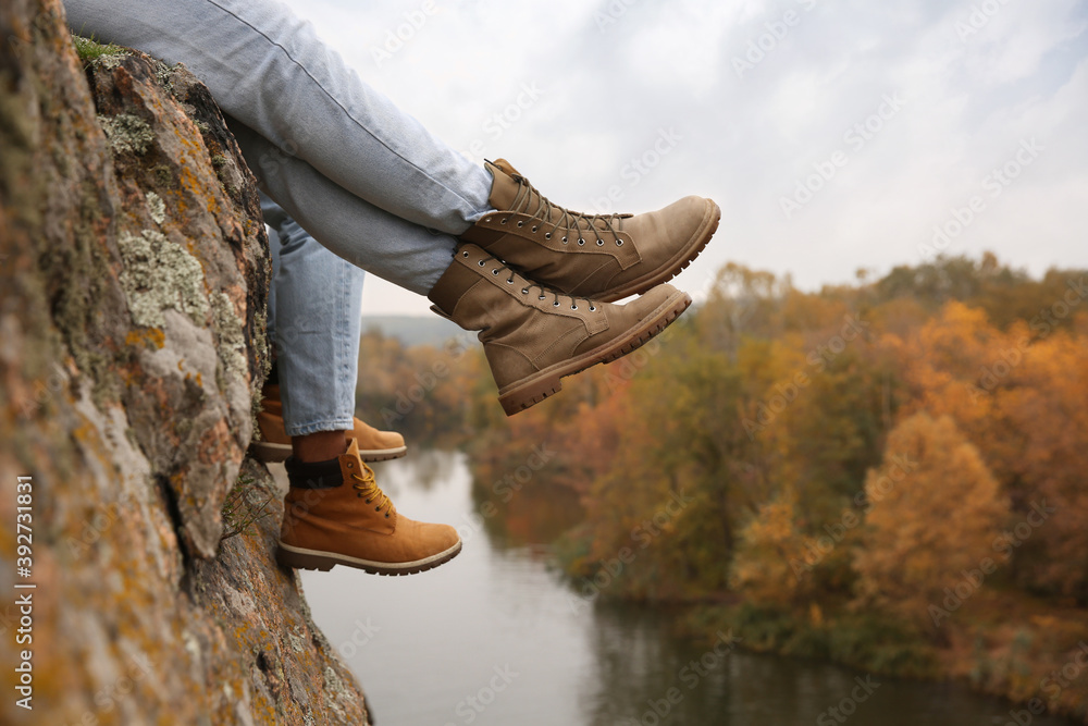 Fototapeta Couple wearing stylish hiking boots on steep cliff, closeup