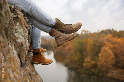 Couple wearing stylish hiking boots on steep cliff, closeup Wallpaper Mural