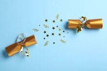 Open Golden Christmas Cracker With Shiny Confetti On Light Blue Background, Top View