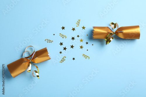 Vászonkép Open golden Christmas cracker with shiny confetti on light blue background, top