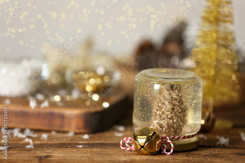 Handmade snow globe and Christmas decorations on wooden table, space for text