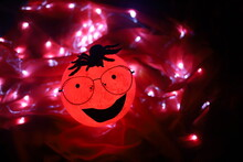 A Very Creepy Cartoon Moon Shaped Round Light Wearing Glasses And A Tarantula Shaped Spider Over It's Head Smiling Isolated On Red Background