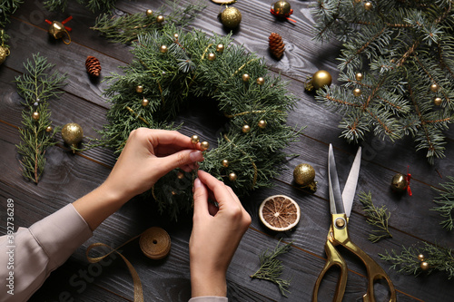 Florist making beautiful Christmas wreath at black wooden table, closeup