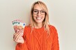 Leinwandbild Motiv Beautiful blonde woman holding 10 euro banknotes looking positive and happy standing and smiling with a confident smile showing teeth