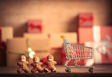 Gingerbread Man And Shoppings Cart On Table With Christmas Gifts On Background